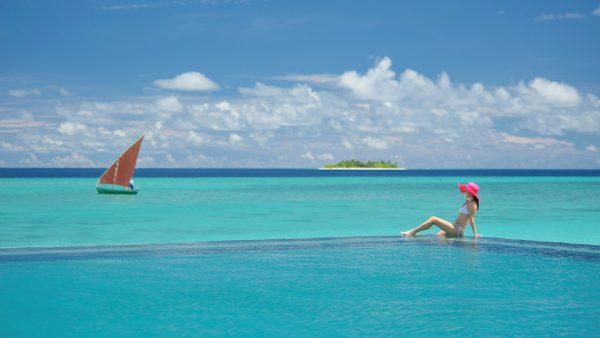 Woman relaxing in the infinity pool gazing. Ayada Maldives luxus Surf resort in the south atoll